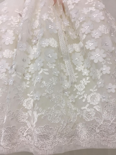 κεντημένα λουλούδια πάνω στη φούστα του βαπτιστικού φορέματος